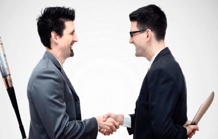 Мужчины улыбаются и жмут друг другу руки, а за спинами держат биты