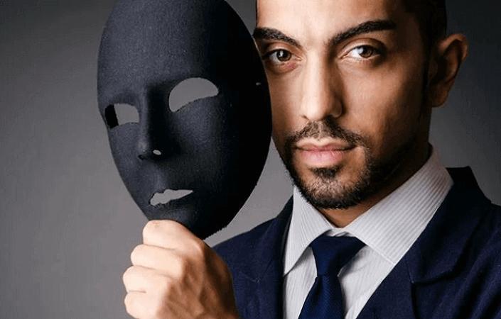 Мужчина в костюме держит около лица черную маску